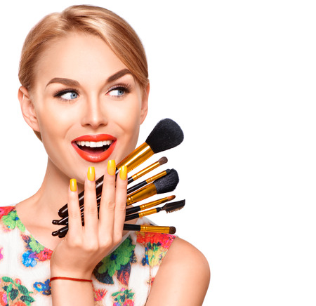 Foto de Beauty woman with makeup brushes. Applying holiday makeup - Imagen libre de derechos