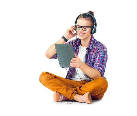 Photo pour Young fashion man sitting on the floor and enjoying music - image libre de droit