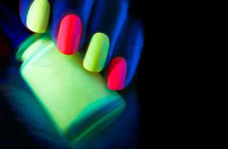 Fluorescent nail polish. Fashion model woman nails in neon light