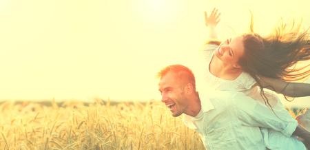 Happy couple having fun outdoors on wheat field over sunset