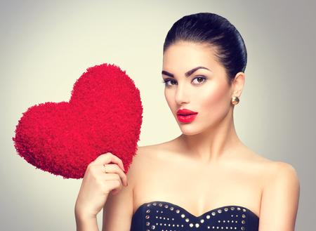 Photo pour Sexy brunette woman holding heart shaped red pillow - image libre de droit