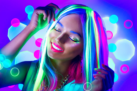 Photo for Young woman dancing in neon light. Beauty model girl with fluorescent make-up - Royalty Free Image