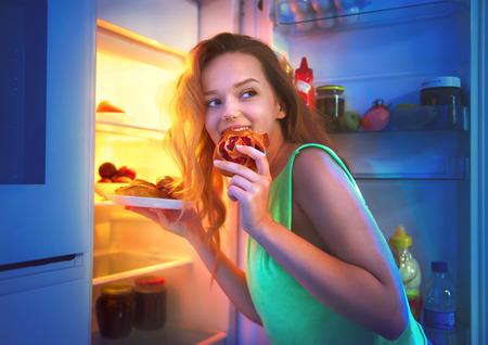 Foto de Beautiful teenage girl taking food from refrigerator at night - Imagen libre de derechos