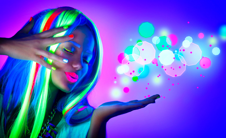 Foto de Fashion woman in neon light. Beautiful model girl with fluorescent make-up - Imagen libre de derechos