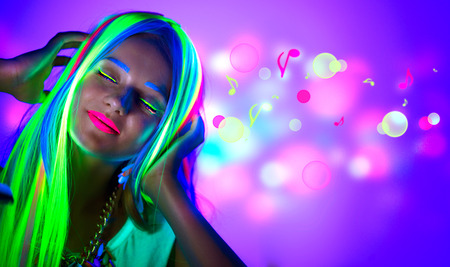 Photo pour Beautiful young woman in neon light. Disco girl with fluorescent make-up - image libre de droit