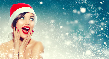 Photo pour Christmas. Beautiful surprised woman in Santa's hat - image libre de droit