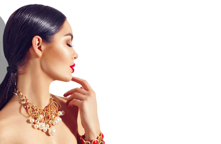 Beauty fashion brunette model girl portrait. Sexy young woman with perfect makeup and trendy golden accessories