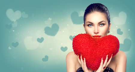 Photo pour Valentine's day. Sexy model girl with heart shaped fluffy red pillow - image libre de droit