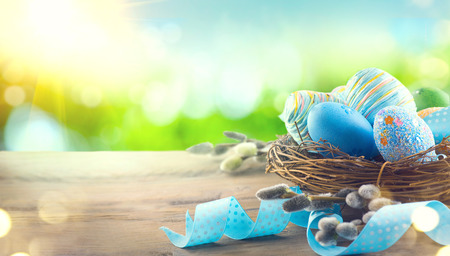 Photo for Easter colorful painted eggs with spring flowers and blue satin ribbon on wooden table top background - Royalty Free Image