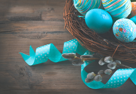 Photo for Easter colorful painted eggs with spring flowers and blue satin ribbon over wooden background - Royalty Free Image
