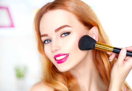 Foto de Beauty woman applying makeup. Beautiful girl looking in the mirror and applying cosmetic with a big brush - Imagen libre de derechos