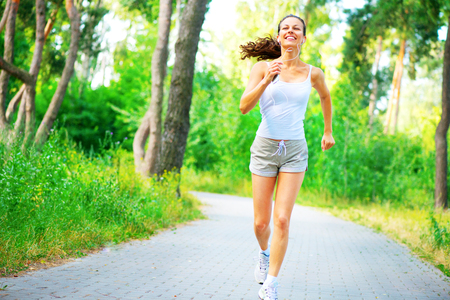 Beauty young woman with earphones running in the park. Full length portrait