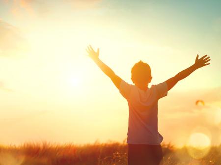 Photo pour Little boy raising hands over sunset sky, enjoying life and nature - image libre de droit