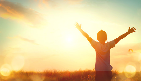 Photo pour Little boy raising hands over sunset sky, enjoying life and nature - image libre de droit