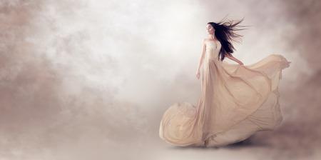 Photo pour Fashion model in beautiful luxury beige flowing chiffon dress - image libre de droit