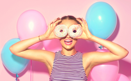 Photo pour Joyful model beauty girl holding donuts and colorful air balloons over pink background - image libre de droit