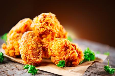Foto de Fried chicken wings and legs on wooden table. Closeup of tasty fried chicken - Imagen libre de derechos