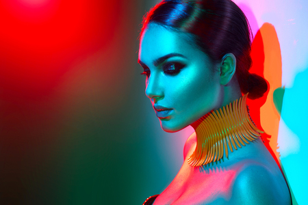 Foto de Fashion model woman in colorful bright lights posing. Portrait of beautiful sexy girl with trendy makeup - Imagen libre de derechos