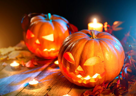 Foto de Halloween pumpkin head jack lantern with burning candles over wooden background - Imagen libre de derechos