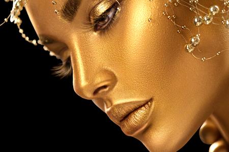 Foto de Beauty model girl with holiday golden shiny professional makeup closeup portrait. Gold jewelry and accessories - Imagen libre de derechos