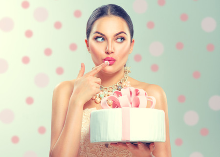 Photo pour Funny joyful beauty model girl holding big beautiful party or birthday cake over green background and tasting it - image libre de droit