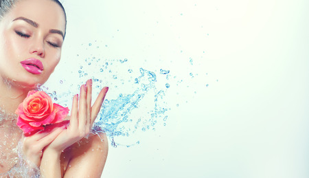 Photo pour Spa woman. Beauty smiling girl with splashes of water and rose in her hands. Skincare concept - image libre de droit
