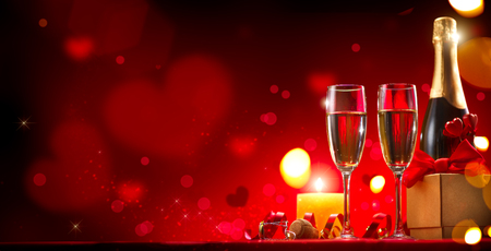 Foto de Valentine's Day romantic dinner. Champagne, candles and gift box over holiday red background - Imagen libre de derechos