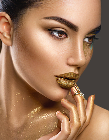 Foto de Fashion art makeup. Portrait of beauty woman with golden skin. Glamour shiny professional makeup - Imagen libre de derechos