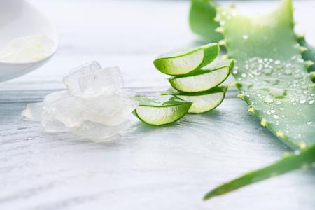 Photo for Aloe Vera gel closeup. Sliced Aloevera natural organic renewal cosmetics, alternative medicine. Organic skincare concept. On white wooden background - Royalty Free Image