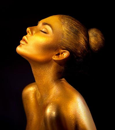 Foto de Fashion art golden skin woman portrait closeup. Gold, jewelry, accessories. Model girl with golden glamour shiny makeup - Imagen libre de derechos