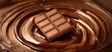 Foto de Chocolate bar over melted dark chocolate swirl liquid background. Confectionery concept backdrop. Sweet dessert - Imagen libre de derechos