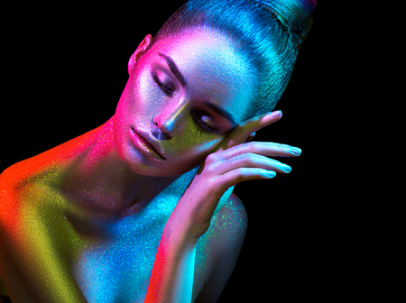 Foto de Fashion model woman in colorful bright sparkles and neon lights posing in studio, portrait of beautiful sexy girl. Art design colorful vivid makeup - Imagen libre de derechos