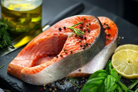 Foto de Salmon. Raw trout fish steak with herbs and lemon on black slate background. Cooking, seafood. Healthy eating concept - Imagen libre de derechos