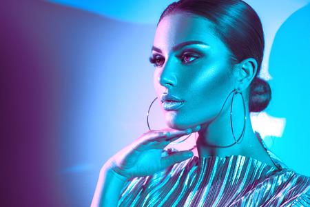 Foto de Fashion model brunette woman in colorful bright neon lights posing in studio. Beautiful sexy girl, trendy glowing makeup, metallic silver lips - Imagen libre de derechos