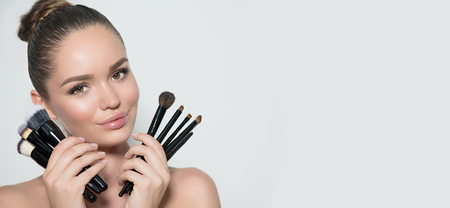 Photo pour Beauty model girl, makeup artist holding set of make up brushes and smiling. Beautiful brunette young woman with perfect skin and nude make-up. Perfect skin - image libre de droit
