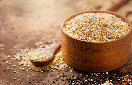Foto de Quinoa. White quinoa grains in a wooden bowl. Healthy food. Dieting concept. Seeds of white, red and black quinoa - Chenopodium quinoa - Imagen libre de derechos