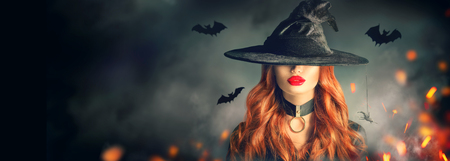Photo pour Beautiful young woman in witches hat with long curly red hair over spooky dark magic forest background - image libre de droit