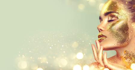 Foto de Beauty fashion model girl with golden skin makeup and body, golden jewelery background. Gold body art. Fashion art portrait - Imagen libre de derechos