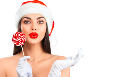 Photo pour Christmas woman. Joyful model girl in Santa's hat with lollipop candy pointing hand, proposing product. Sales. Surprised expression. Closeup portrait isolated on white background - image libre de droit