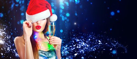 Photo pour Christmas sexy woman. Beauty model girl in Santa's hat with glass of champagne in her hand celebrating on blinking holiday winter wide background - image libre de droit