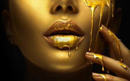 Foto de Golden paint smudges drips from the face lips and hand, golden liquid drops on beautiful model girl's mouth, creative abstract makeup. Beauty woman face - Imagen libre de derechos