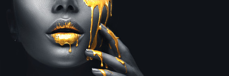 Photo pour Golden paint smudges drips from the face lips and hand, golden liquid drops on beautiful model girl's mouth, creative abstract makeup. Beauty woman face - image libre de droit