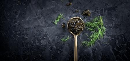 Photo pour Black caviar in a spoon on dark background. Natural sturgeon black caviar closeup. Delicatessen. Top view, flatlay - image libre de droit