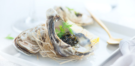 Foto de Fresh oysters with black caviar. Opened oysters with black sturgeon caviar. Gourmet food. Delicatessen - Imagen libre de derechos