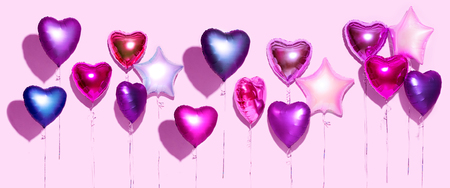 Photo pour Air balloons. Bunch of purple heart shaped foil balloons, isolated on pink background. Valentine's day background. Wide screen - image libre de droit