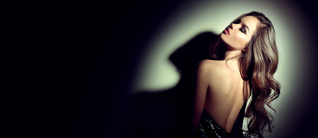 Photo pour Sexy young woman portrait. Seductive brunette girl posing in darkness. Beauty glamour lady with long curly hair in spotlight - image libre de droit