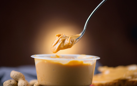 Photo pour Peanut butter. Creamy smooth peanut butter in a jar on a table. Spoon of Natural nutrition. Organic food. American cuisine - image libre de droit
