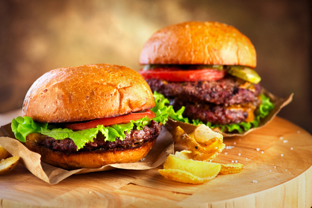 Photo for Hamburger and Double Cheeseburger with fries wooden table - Royalty Free Image