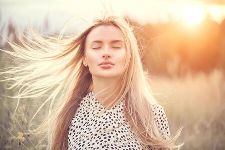 Photo for Portrait of beauty girl with fluttering white hair enjoying nature outdoors. Flying blonde hair on the wind. Beautiful young woman face closeup - Royalty Free Image