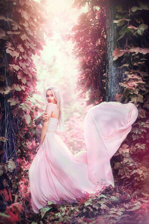 Photo pour Beauty romantic young woman in long chiffon dress with gown posing in fantasy misty forest. Beautiful happy bride model girl enjoying nature outdoors - image libre de droit